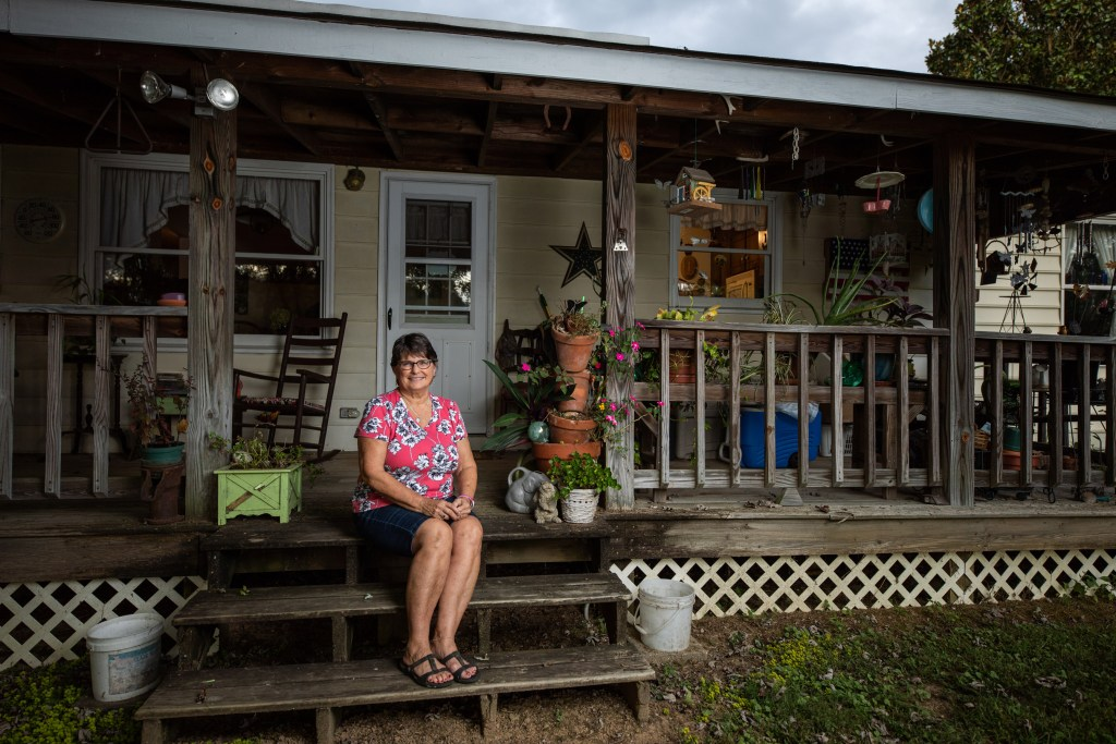 A photo of a woman sitting on her decorated back porch.