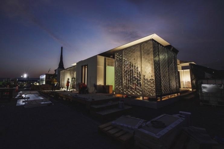A photo of a futuristic house, illuminated at night against a dramatic blue and purple night sky.