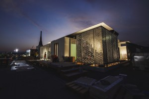 A photo of a cutting-edge house being built in a desert at dusk.