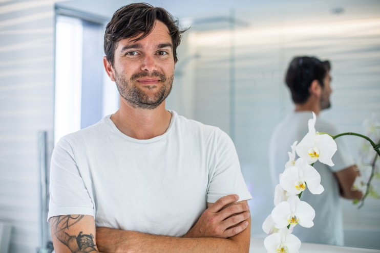 A photo of a young man with scruff, crossing his arms, wearing a white shirt, and smiling for a photo in front of a mirror background.