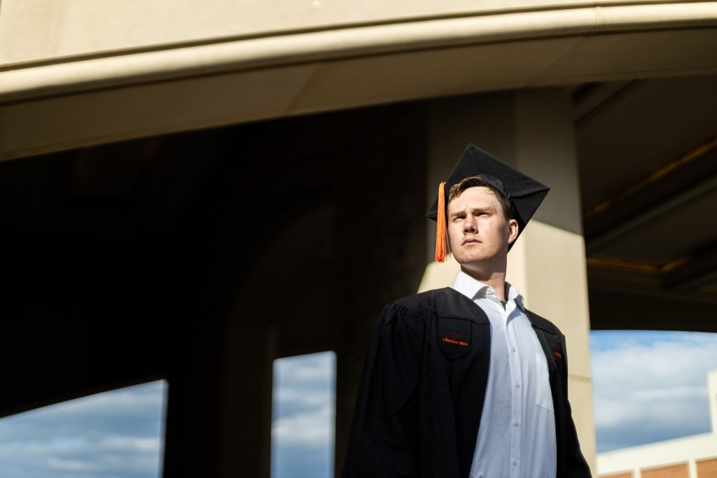 A photo of a young man looking off into the distance, wearing a graduation cap.