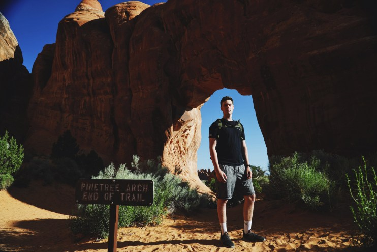 """A photo of a young man standing in front of an arch. A sign in front of him reads """"Pinetree Arch. End of trail."""""""