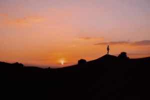 A photo of a desert sunset, with a man's silhouette atop a peak.