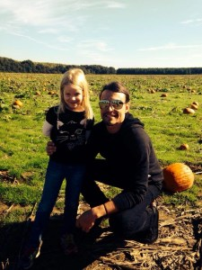 Dwain and his daughter in a pumpkin patch.
