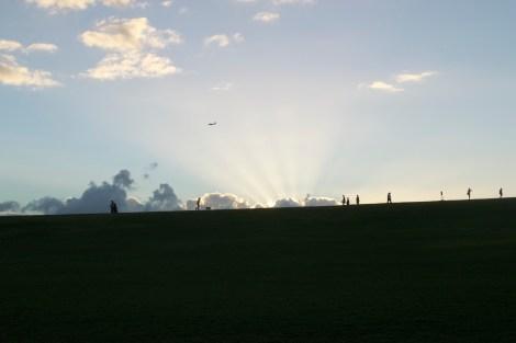 families enjoying sunset at park