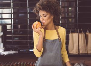black woman smelling tangerine to press tangerine essential oil