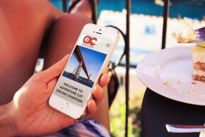 photo of hand holding a phone, showing mobile website for Adventure Cat Sailing Charters