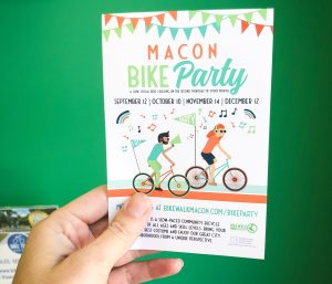 photo of hand holding a 'Macon Bike Party' flyer for Bike Walk Macon