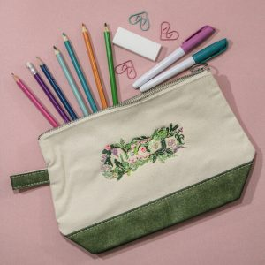 Macon Floral design embroidered on a green and natural canvas zipper pouch with pencils and other school supplies, Macon gift idea for girls and teens
