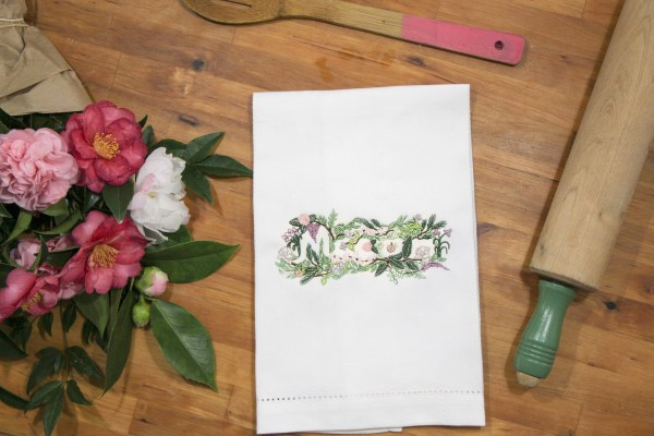 image of Macon Floral embroidery stitched onto a kitchen towel next to flowers and a rolling pin, Macon gift or souvenir