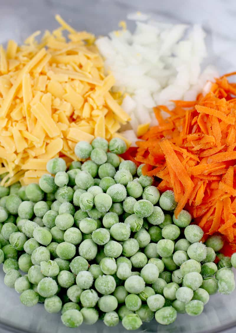 peas, shredded cheese, diced onion, and shredded carrot in a bowl