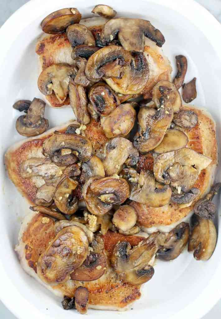 top view of browned mushrooms on the seared chops in a white bake dish