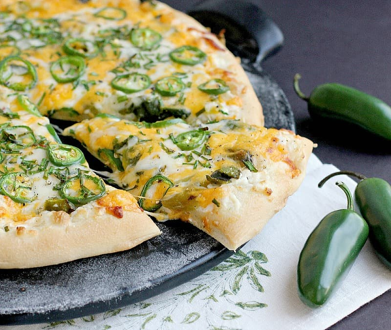 side view of the finished jalapeno pizza on a black pizza stone with one slice cut and nudged out a bit to show melty cheese. a white napkin with green stencil and fresh jalapenos are placed as decoration