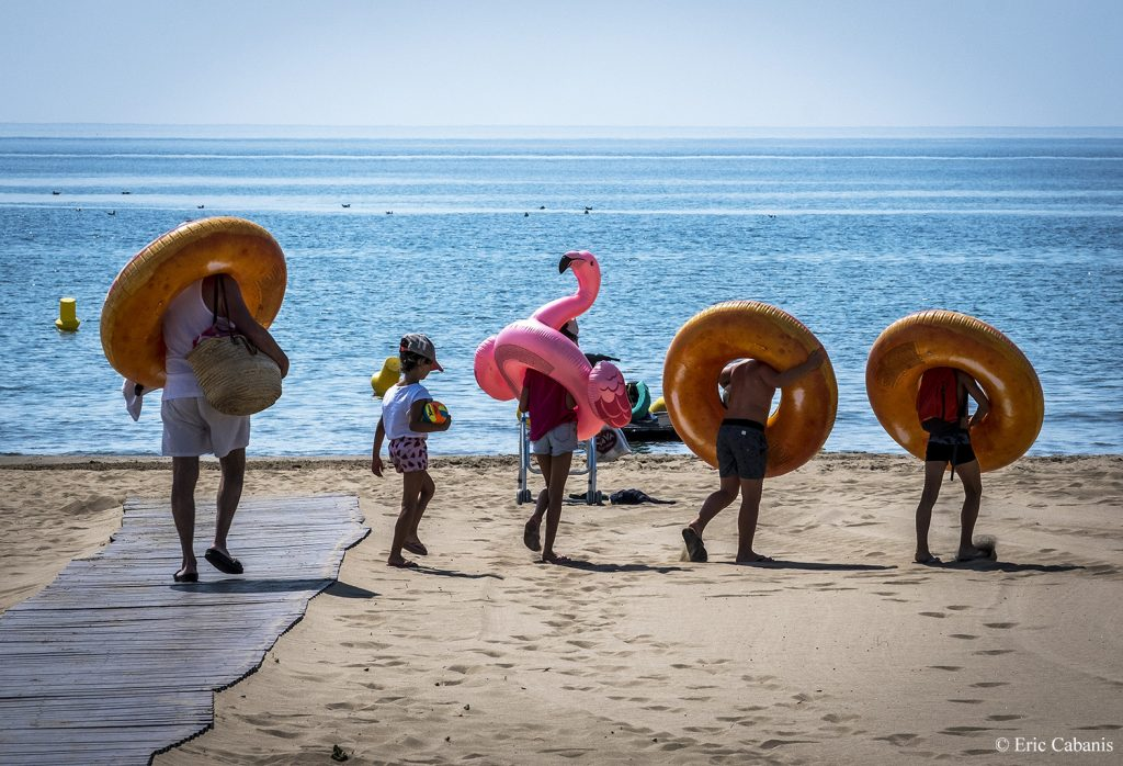 Une famille se rend à la plage avec des bouées géantes en juillet 2019 à Narbonne-Plage A family goes to the beach with giant buoys in July 2019 at Narbonne-Plage Photojournalism Streetphotogtraphy Eric Cabanis