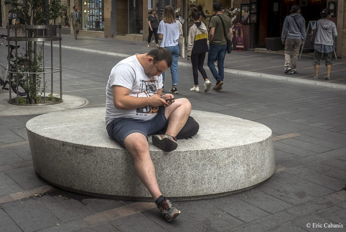 Assis dans une rue du centre ville de Toulouse un homme consulte son téléphone le 1er août 2019 Sitting in a street in downtown Toulouse a man consults his phone on August 1, 2019 Photojournalism Streetphotography Eric cabanis
