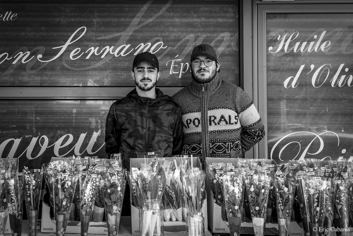 Deux jeunes hommes posent devant leur étal de muguet qu'ils vendent à l'occasion du 1er mai 2019 à Toulouse Two young men pose in front of their lily of the valley stall on 1 May 2019 in Toulouse Photojournalism Streetphotography Eric Cabanis