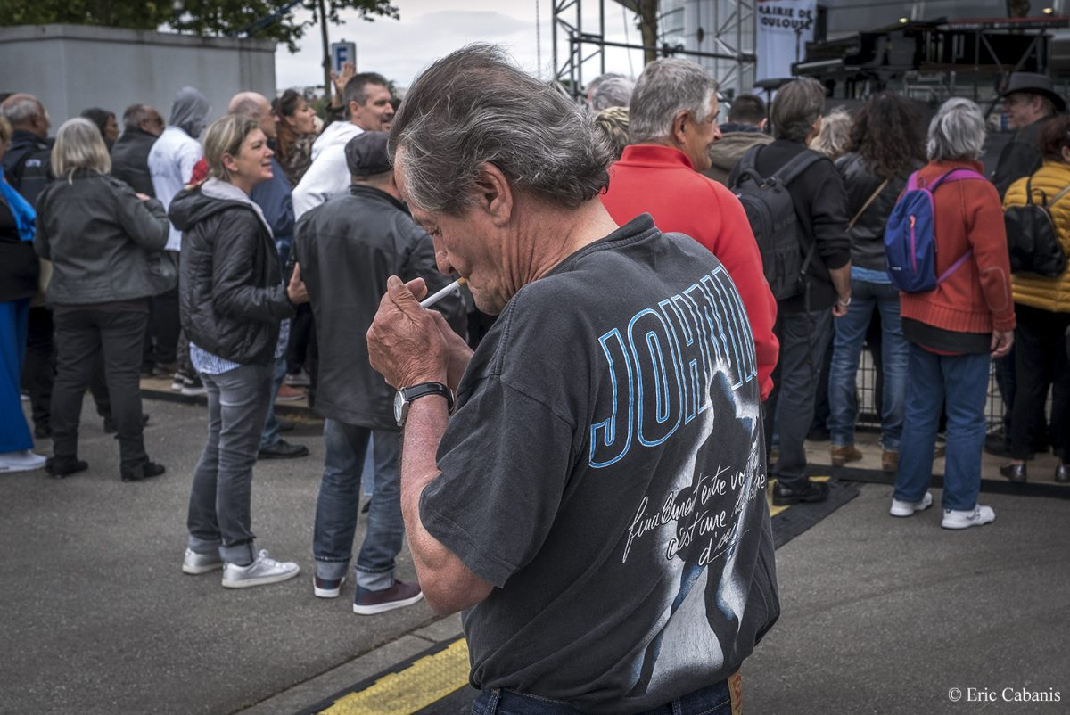 Un fan du chanteur Johnny Hallyday allume une cigarette, le 15 juin 2019, sur l'esplanade du Zénith de Toulouse à l'occasion de l'inauguration de l'esplanade Johnny-Hallyday A fan of the singer Johnny Hallyday lights a cigarette on 15 June 2019 on the esplanade of the Zénith in Toulouse to mark the inauguration of the Johnny Hallyday esplanade Photojournalism Streetphotography Eric cabanis