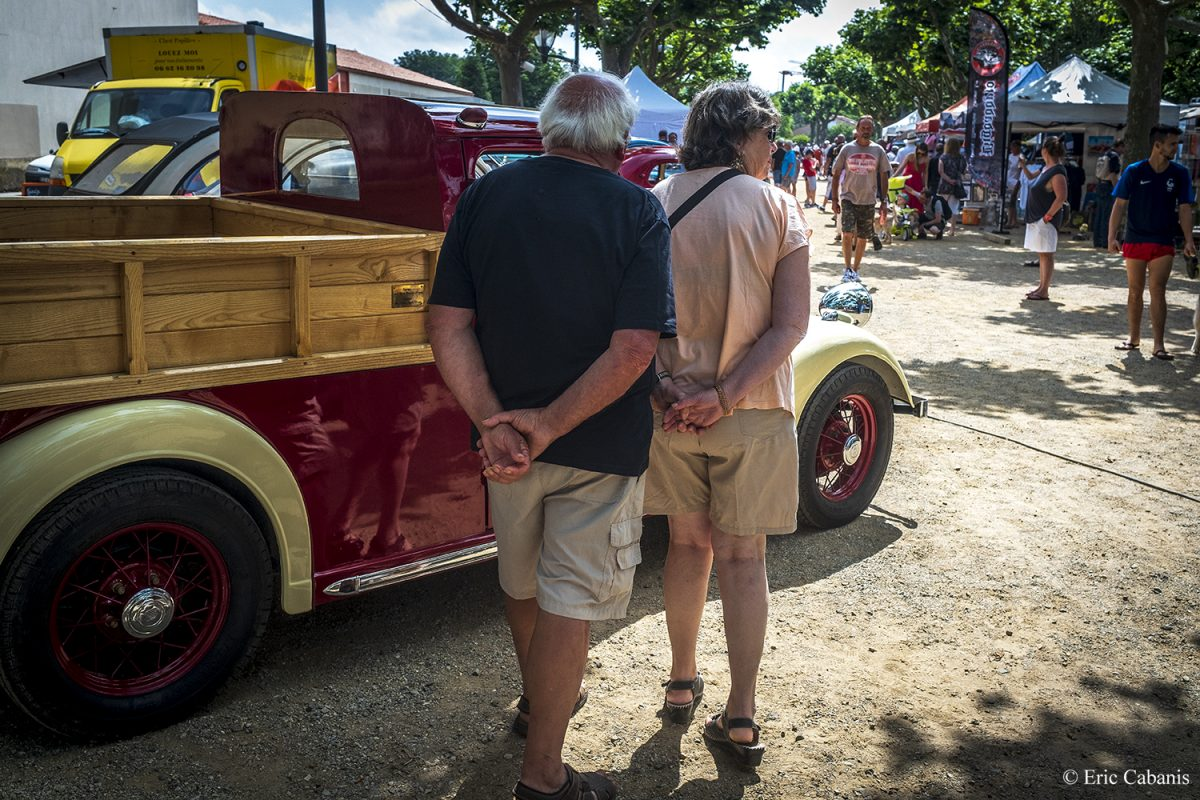 Un couple regarde des voitures des années 50 lors d'un rassemblement de vieilles voitures en mai 2019 à Baziège près de Toulouse A couple looks at cars from the 50's during a gathering of old cars in May 2019 in Baziège near Toulouse Photojournalism Streetphotography Eric Cabanis