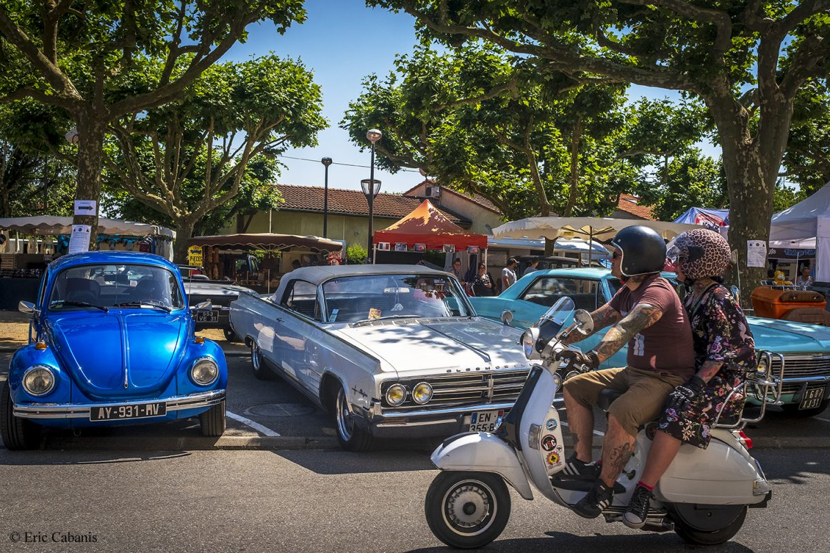 Un couple passe en scooter devant des voitures des années 50 lors d'un rassemblement de vieilles voitures en mai 2019 à Baziège près de Toulouse A couple riding a scooter in front of 50's cars at a rally of old cars in May 2019 in Baziège near Toulouse. Photojournalism Streetphotography Eric cabanis