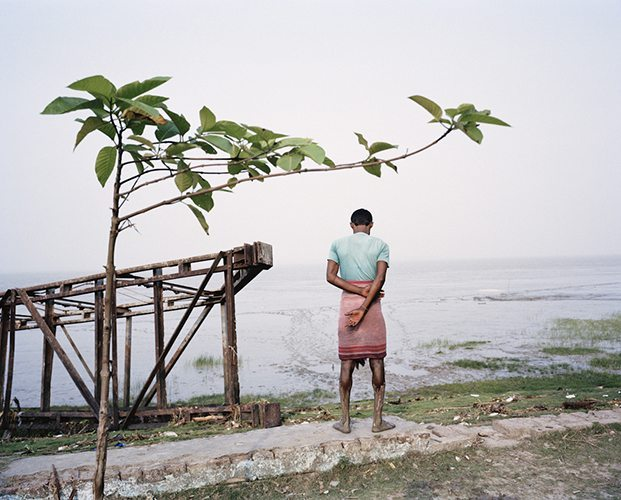 A fish farmer stands before the Hooghly River after working in the river to catch fish, near where the river empties into the Bay of Bengal. While geographically the Ganges River flows into Bangladesh, the spiritual aspect of the river remains within the Hooghly River, which flows through Kolkata and into the Bay of Bengal. Photo by