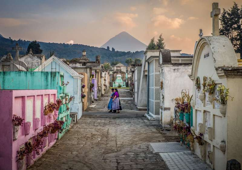 A photo from the rough but beatiful cementary in Xela, Guatemala. In the center 2 mayan ladies are walking with there traditional funeral clothing. In the background you can see the Santa Maria volcano.