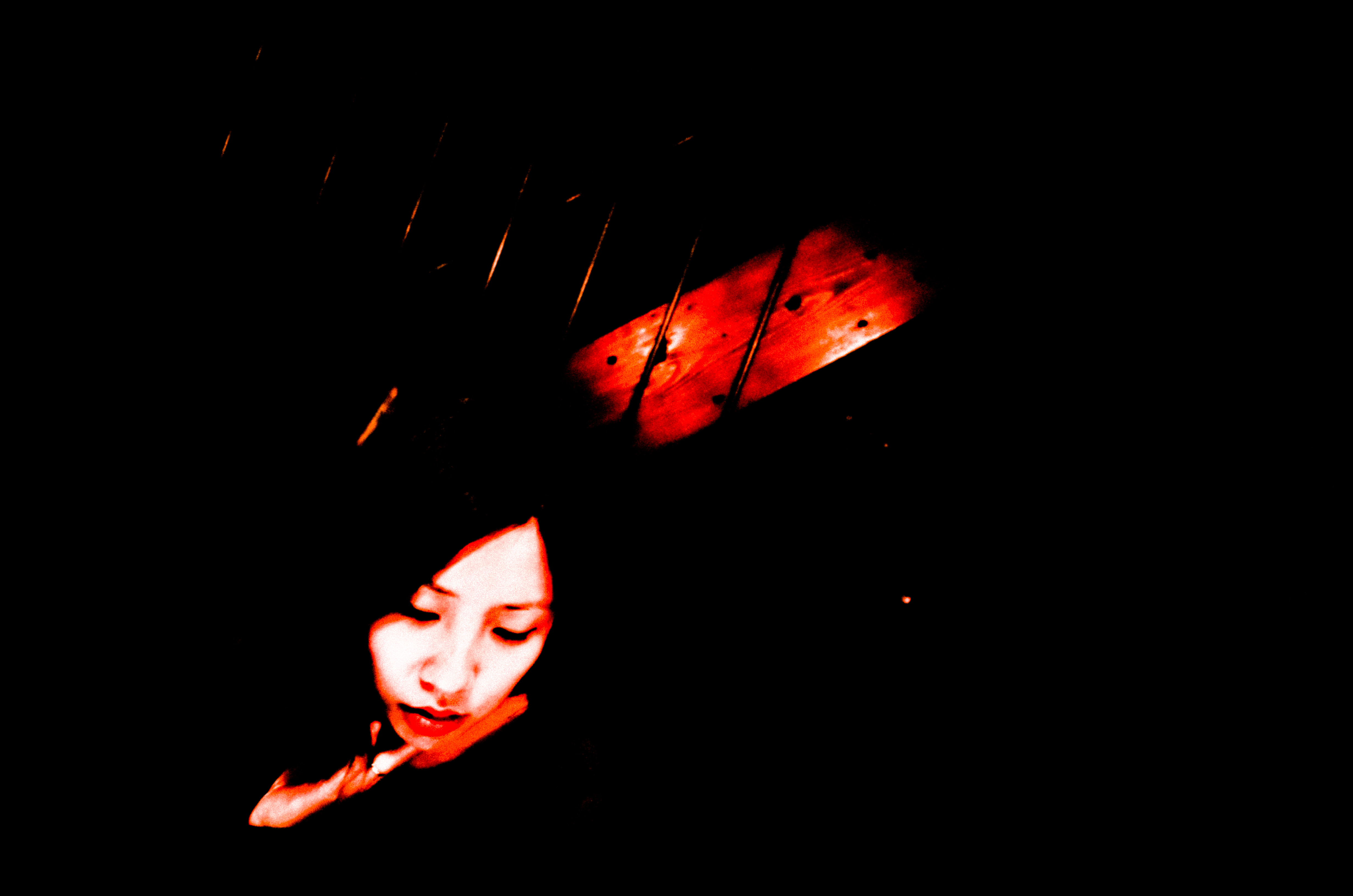 Cindy at work at cafe, with red light. Kyoto, 2017