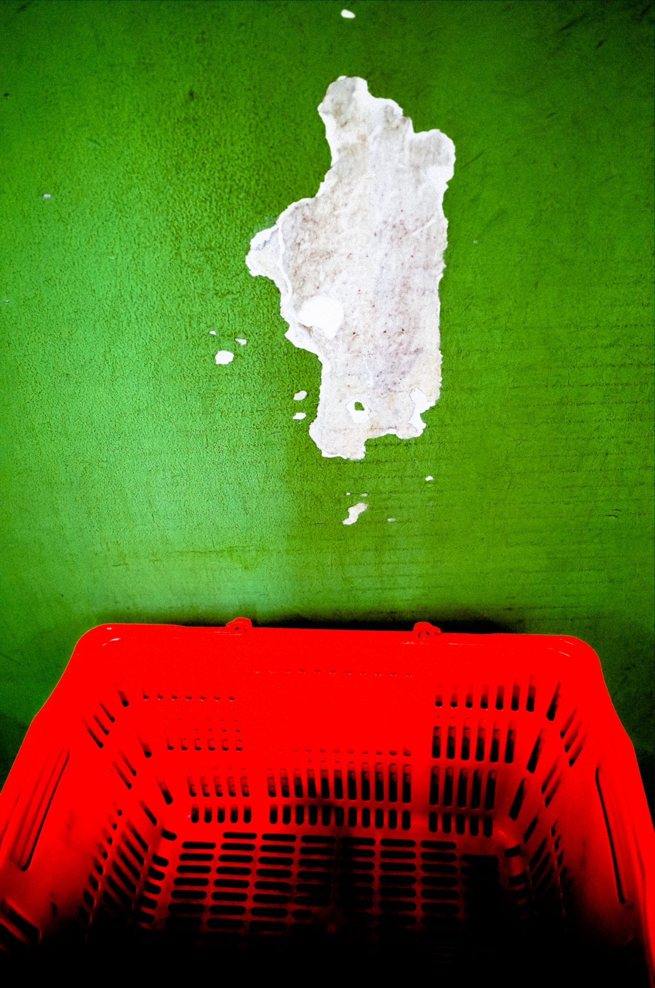 Red wall and green basket inside grocery store. Kyoto, 2017