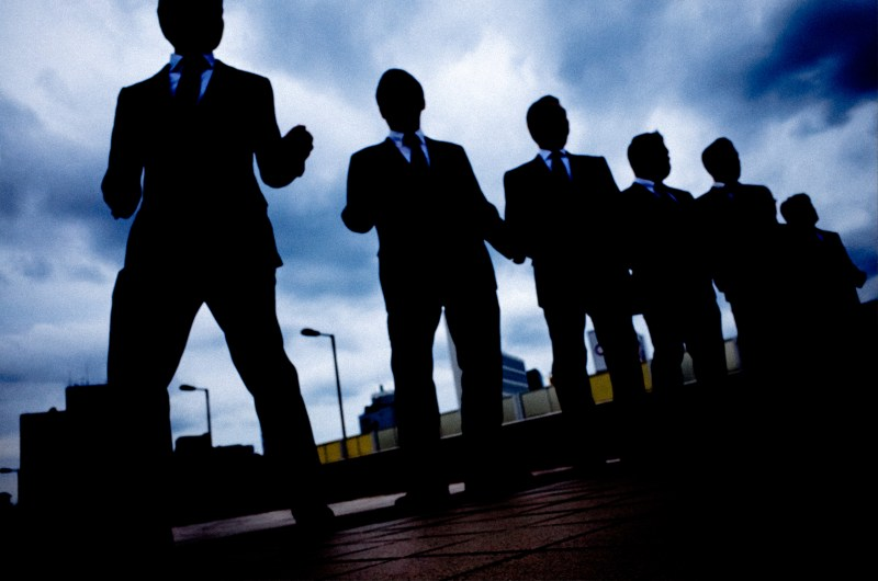 Silhouette of men in suits, lined up. Ueno, Tokyo 2017