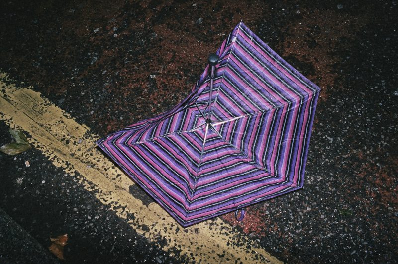 Purple umbrella on the floor with yellow sidewalk line.