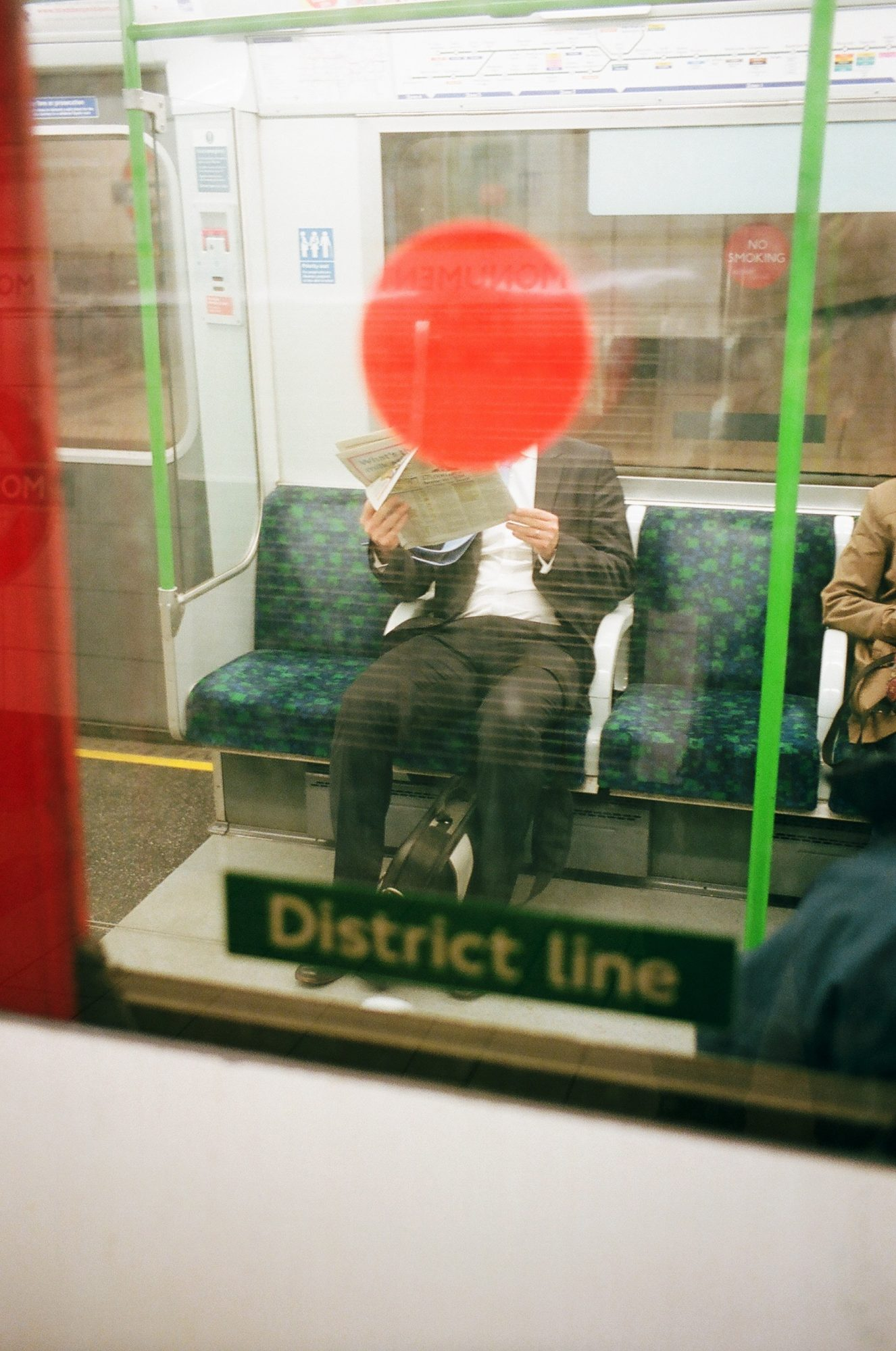 Red dot on head of suit. London tube, 2014