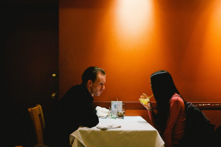 Man and woman having dinner with orange wall. NYC, 2015