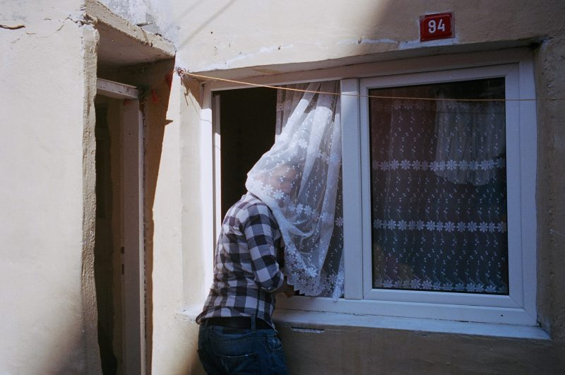 Man with curtain on face. Istanbul, 2013