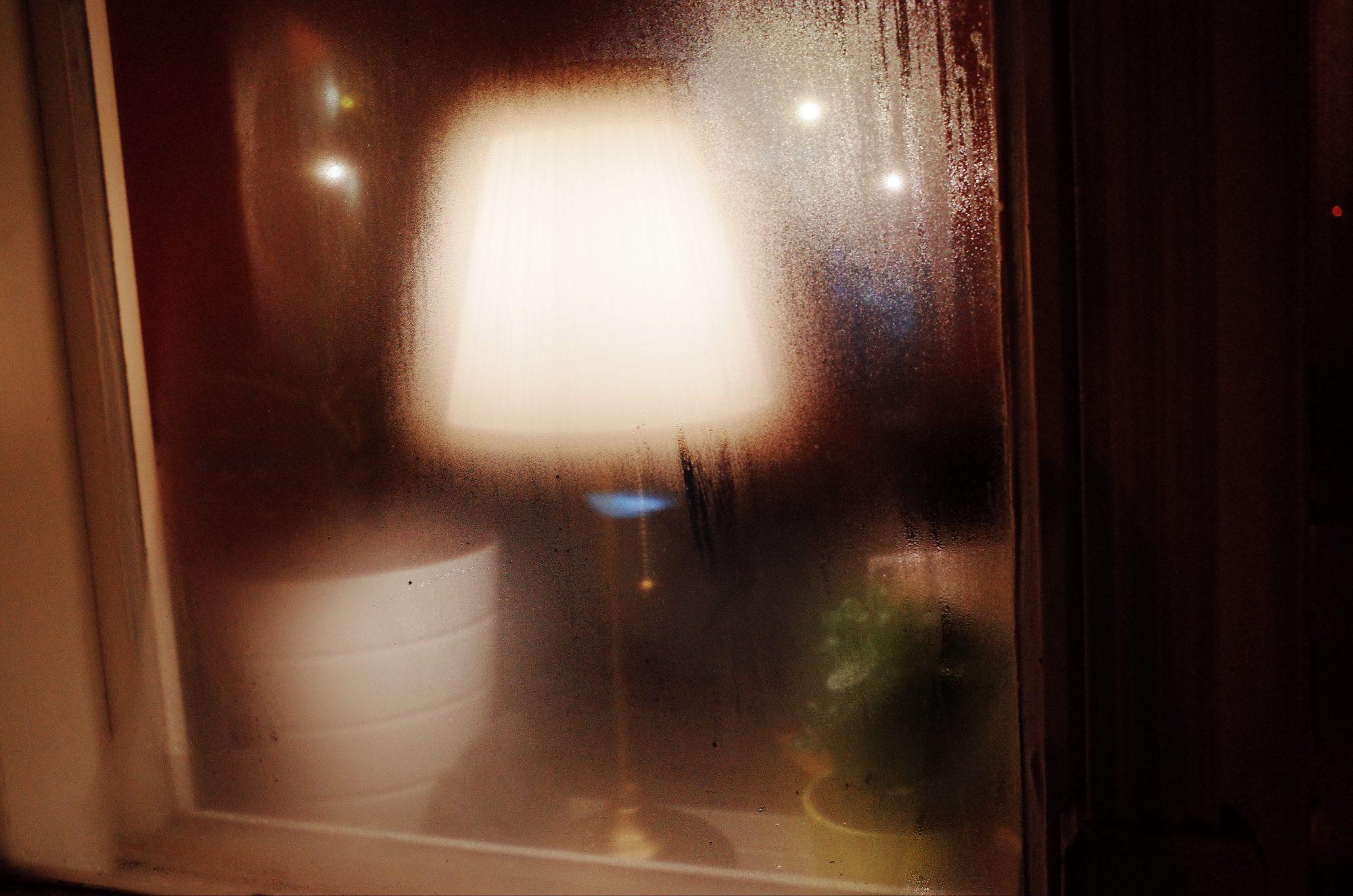 Foggy lamp through window. Prague, 2017