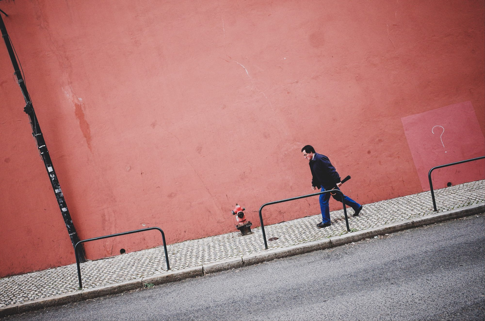 Walking man with pink wall. Dutch angle (tilted) composition. Lisbon, 2018