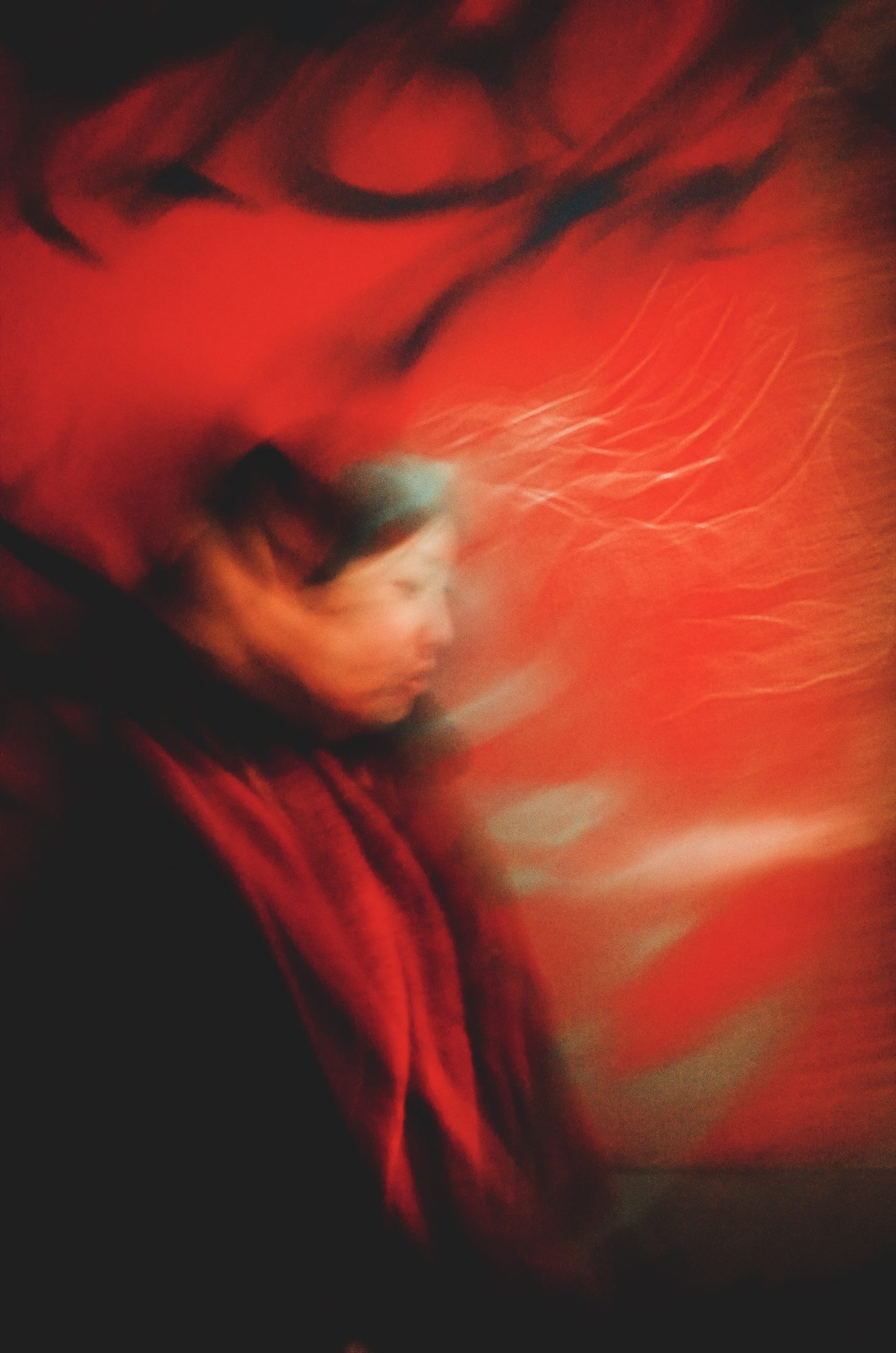 Blurry Cindy walking, with red background, and a touch of green. Lisbon, 2018