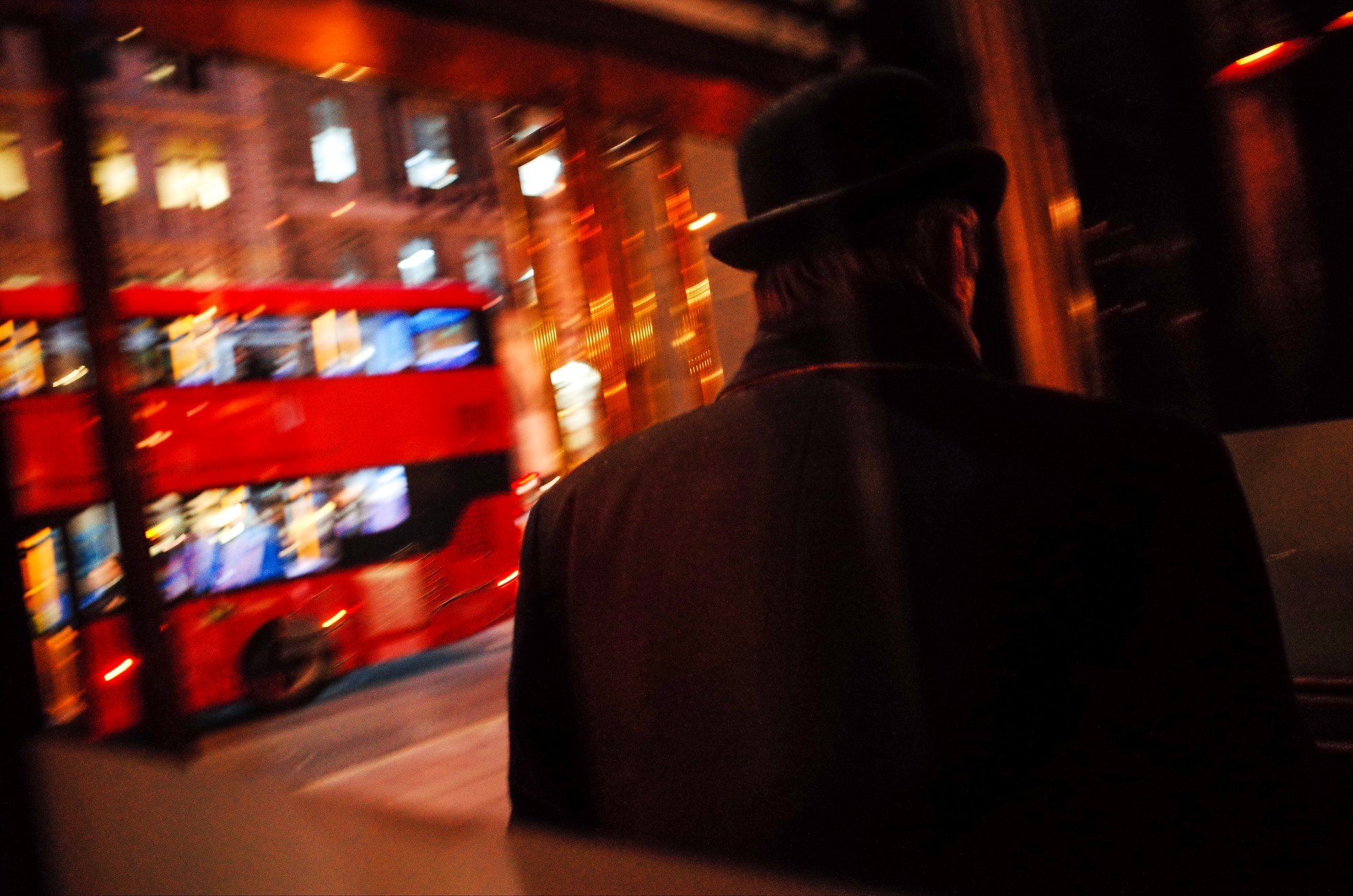 Man in bowler hat. Night street photo, London 2018