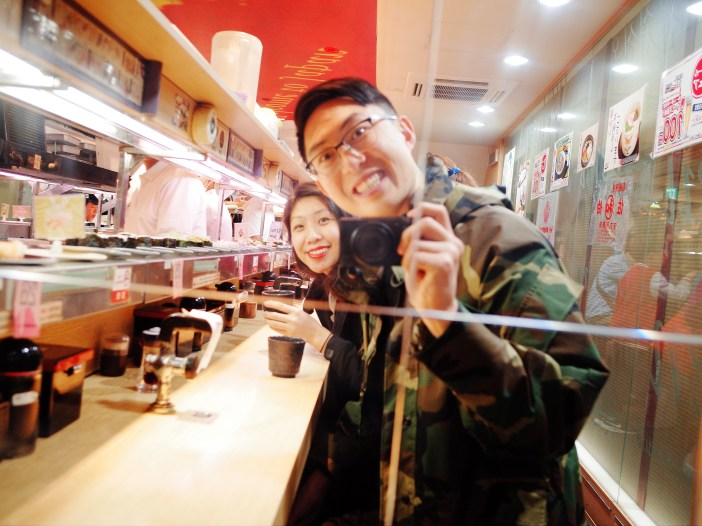 Selfie in the mirror with Cindy at conveyer belt sushi. Osaka, 2018