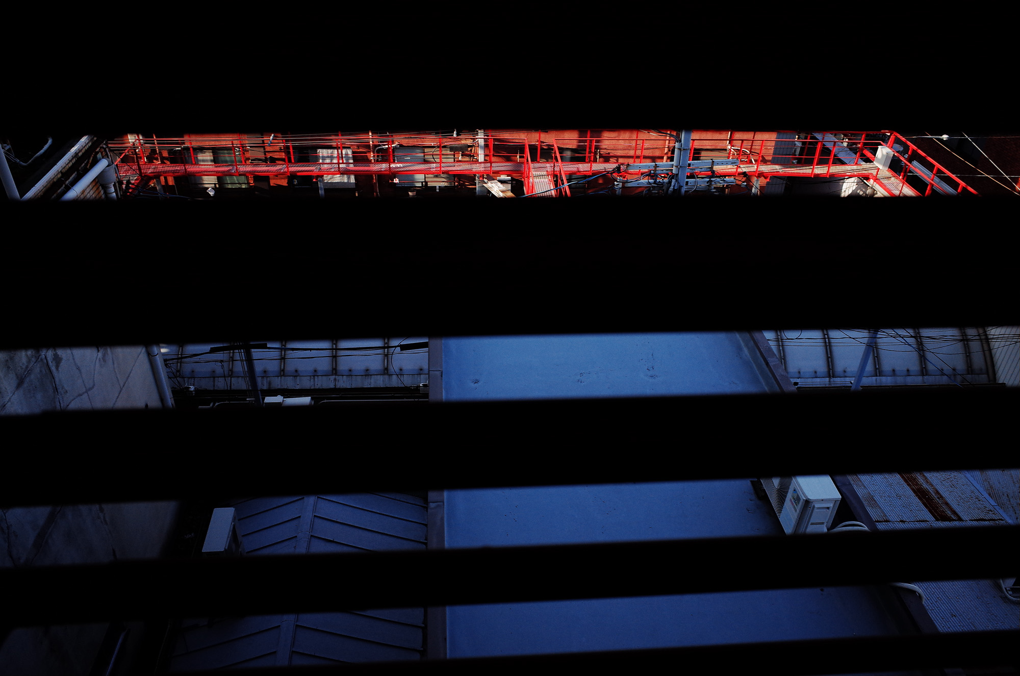 Red and blue abstract, shot from a high staircase, looking through slits, and capturing things far away in the background. Osaka, 2018