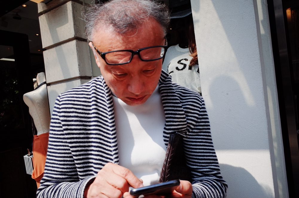 Man with glasses looking at phone. Osaka, 2018