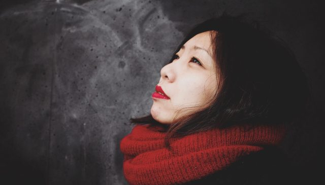 Cindy wearing a red scarf with red lipstick against grey and white wall in Berlin germany