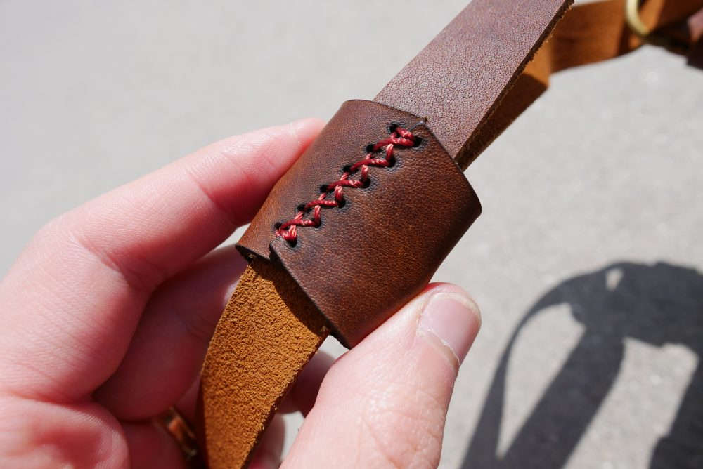 Closeup of burgundy-crimson stitching on the inside of the Henri Shoulder Strap (CREMA BROWN)