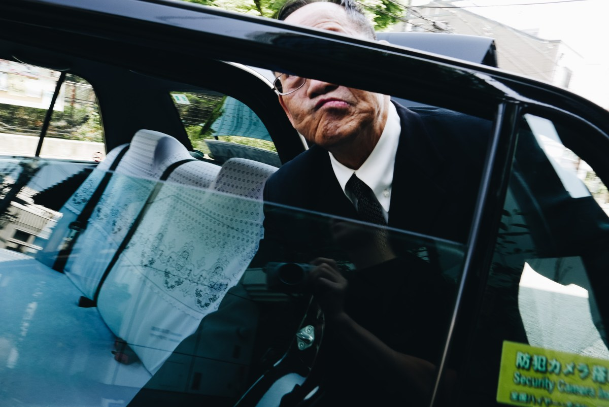 Taxi driver and frame covering face. Kyoto, 2018