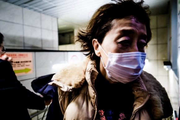 Woman with face mask in Tokyo subway. 2018