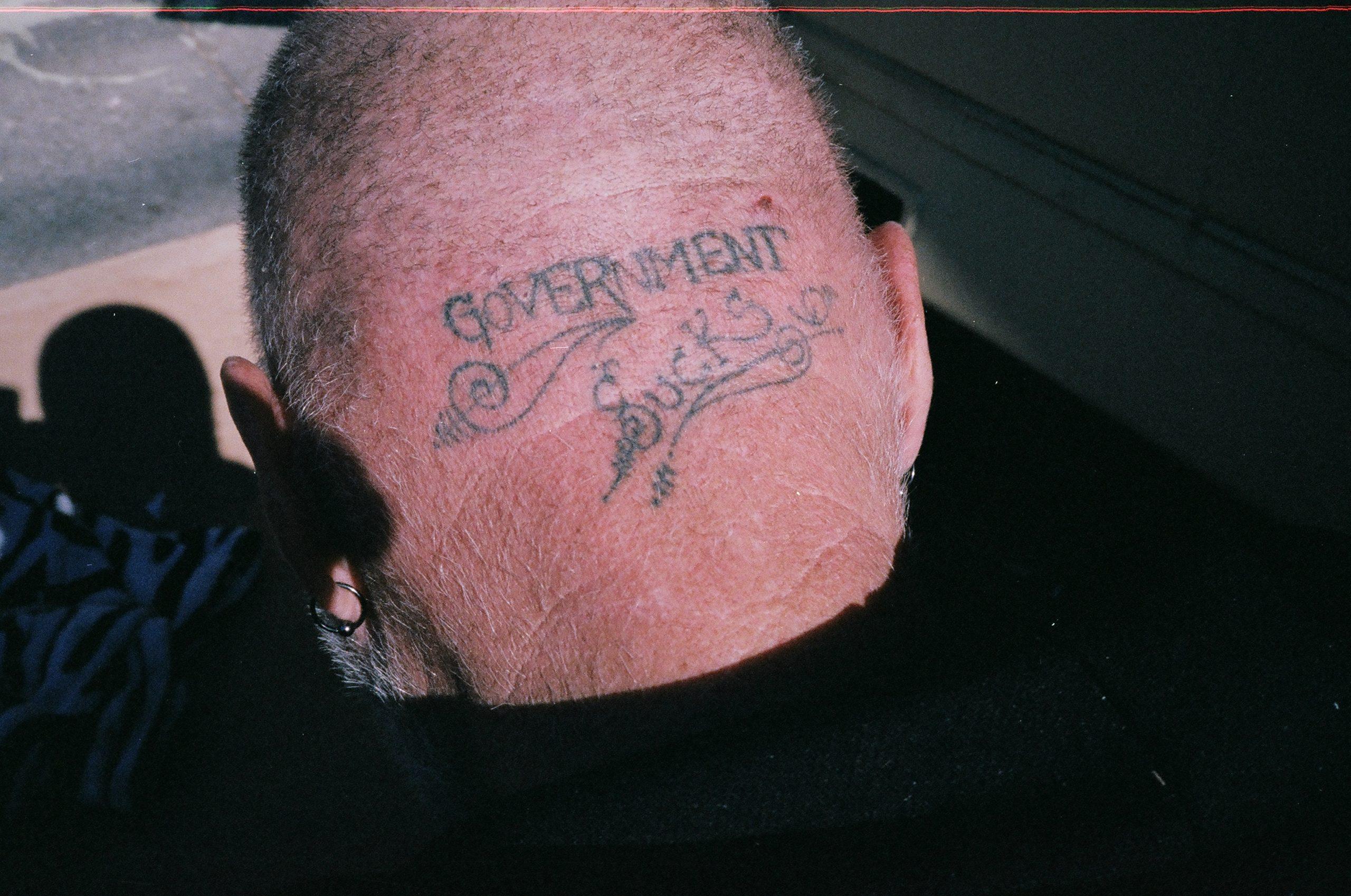 The back of a homeless man's head. Government Sucks. Berkeley, 2014