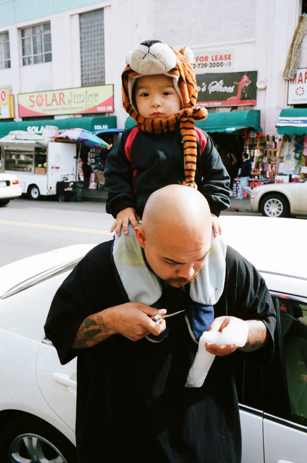 Downtown LA father and son. Father opening popsicle with knife, 2011 #portra400