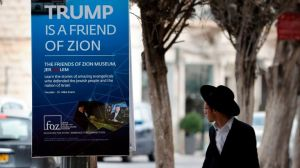 An Ultra-Orthodox Jewish man walks past a poster welcoming and supporting US President Donald Trump