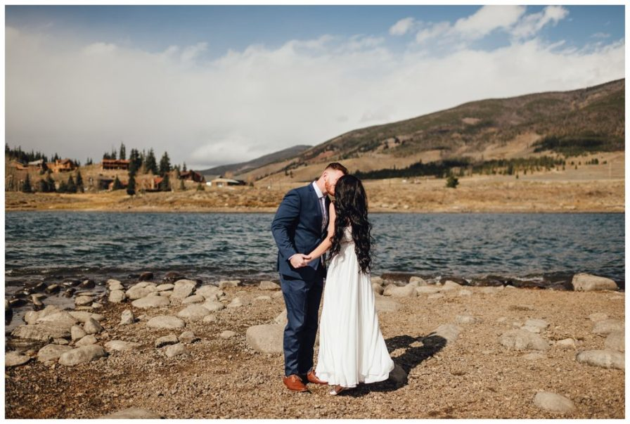 Bride and groom kiss beside Dillon Reservoir