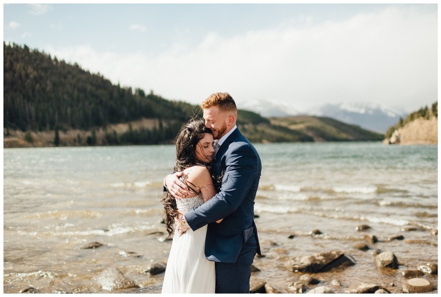 Groom holds his bride to warm her up from the chilly October wind.