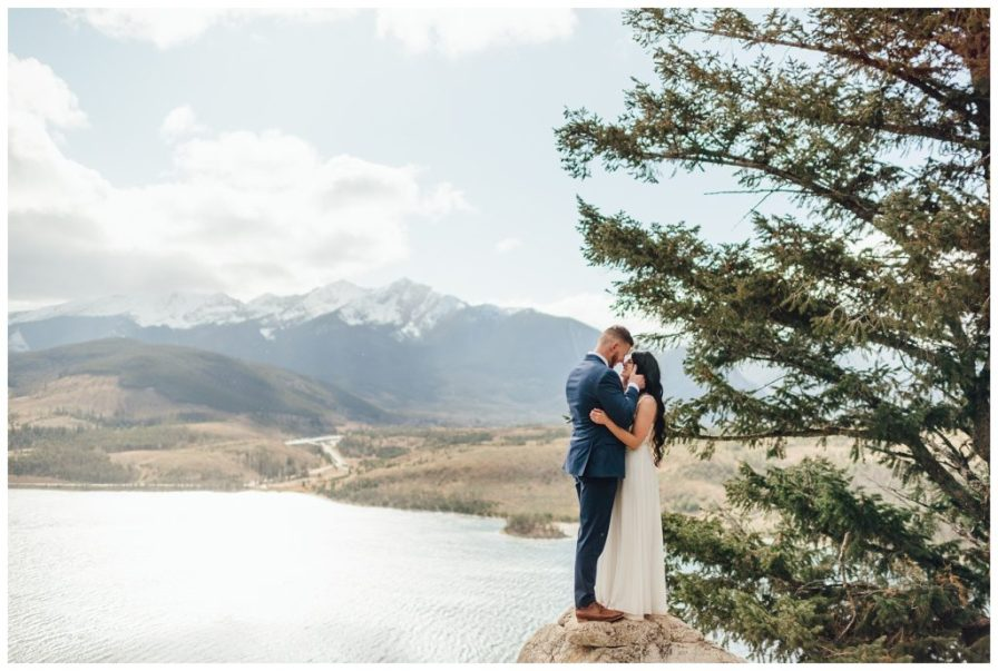 Adventurous bride and groom crawl up the rocks for romantic photos
