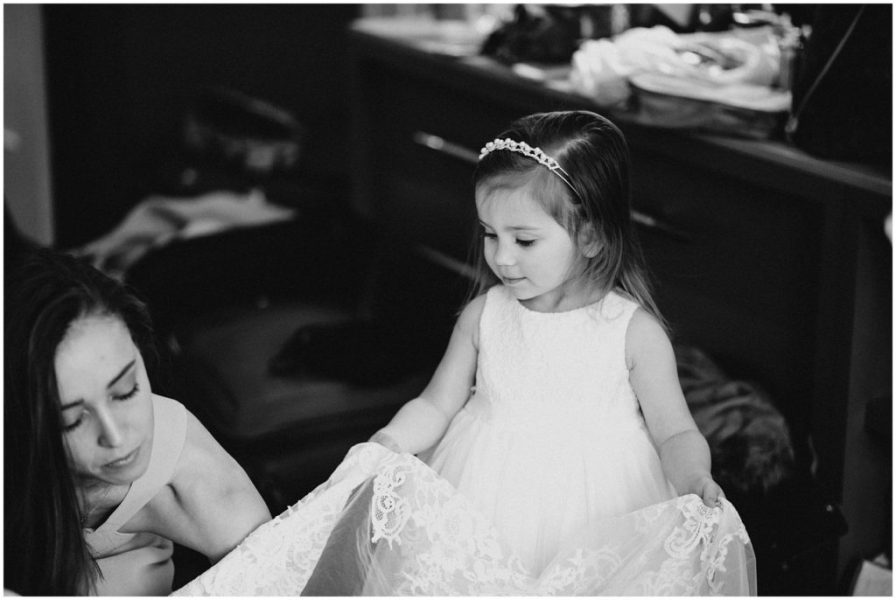 Bridesmaid helping this little girl with her dress